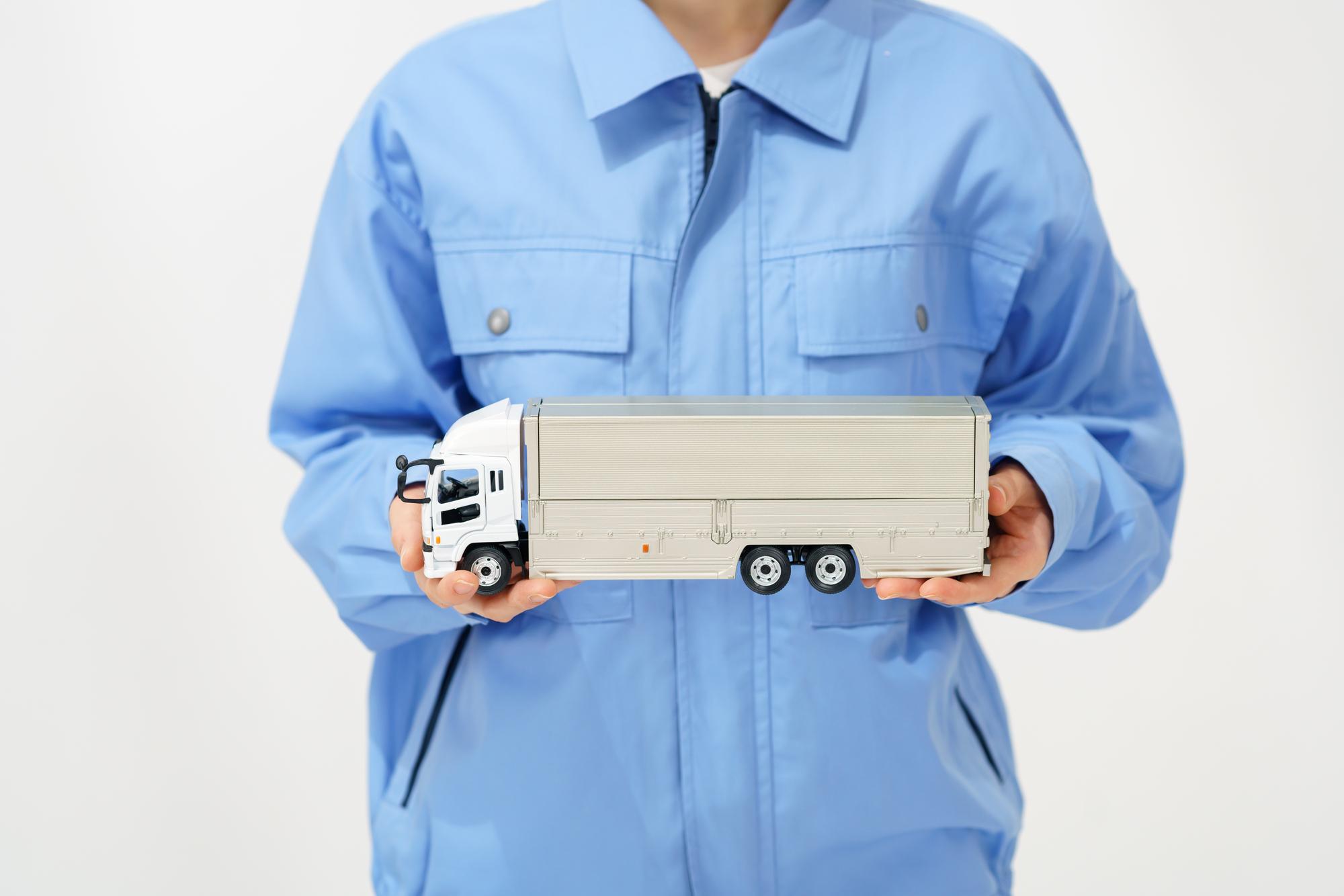 トラックの模型を持った人